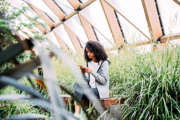 Frau, die in einem schönen garten unter verwendung des mobiltelefons sitzt