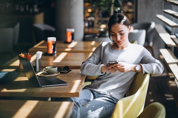 Frau, die in einem trinkenden kaffee des cafés sitzt und an einem computer arbeitet
