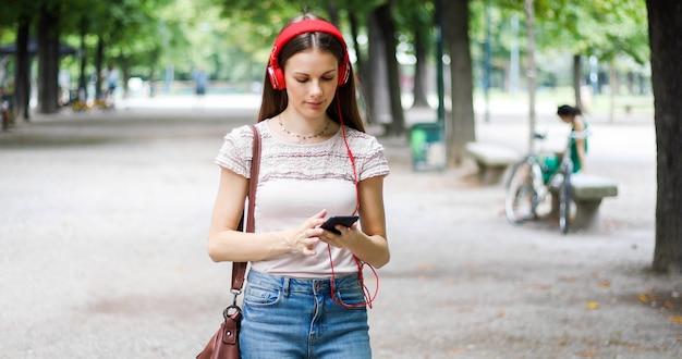 Frau, die in einen park bei der anwendung ihres smartphone geht, um musik zu hören