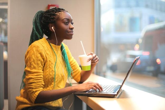 Frau, die in einer bar zu mittag isst, musik hört und ihren laptop verwendet