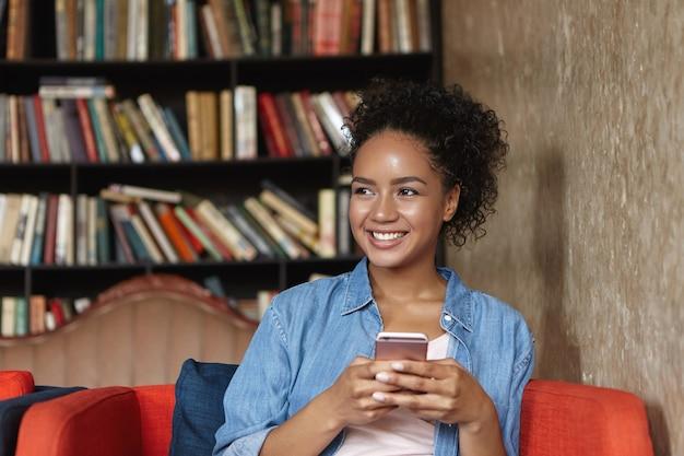 Frau, die in einer bibliothek auf einer couch sitzt