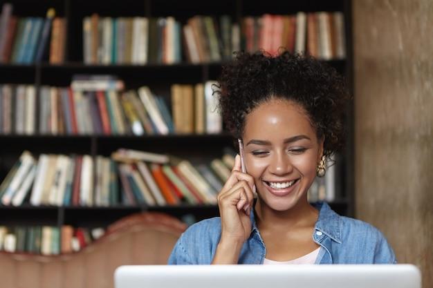 Frau, die in einer bibliothek mit ihrem laptop sitzt
