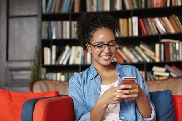 Frau, die in einer bibliothek mit ihrem telefon sitzt