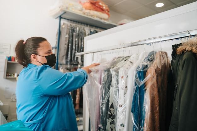 Frau, die in einer chemischen reinigung arbeitet, die nach dem bügeln kleider auf kleiderbügel legt