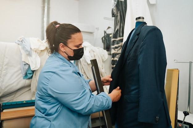 Frau, die in einer chemischen reinigung arbeitet und eine jacke in einen speziellen trockner legt