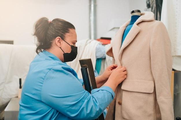 Frau, die in einer chemischen reinigung arbeitet und einen mantel in eine spezielle trocknungsmaschine legt