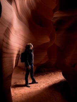 Frau, die in einer höhle, tse bighanilini, obere antilopen-schlucht, antilopen-schlucht, seite, arizona, usa steht