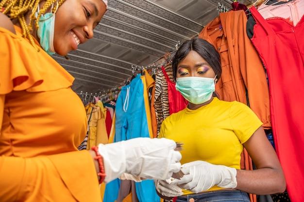 Frau, die in einer lokalen boutique geld zählt und eine gesichtsmaske trägt, um sich vor dem covid-19-coronavirus zu schützen