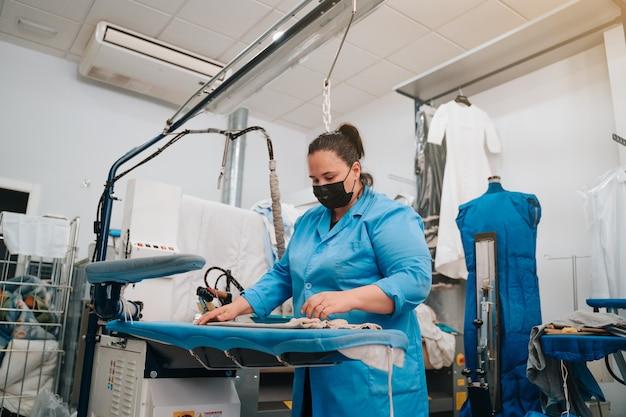 Frau, die in einer reinigung arbeitet und in ihrem geschäft kleidung bügelt