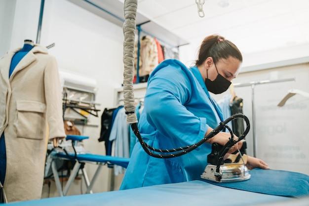 Frau, die in einer reinigung arbeitet und kleidung bügelt