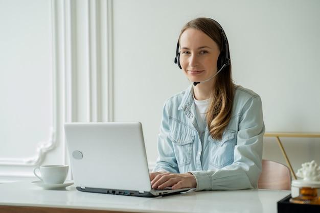 Frau, die in einer videokonferenz online mit einem headset mit mikrofon und unter verwendung eines laptops im büroberatungsklienten spricht