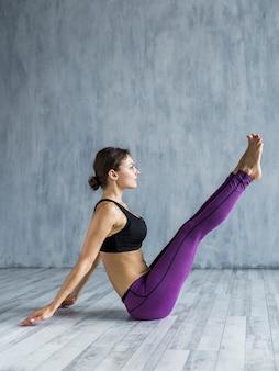 Frau, die in einer yogahaltung sitzt