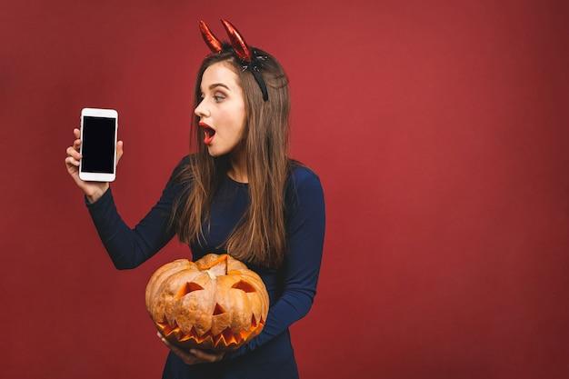Frau, die in halloween-kostüm des schwarzen teufels mit hexenstirnband für eine thematische partei anzieht. sie hält kürbis für ein