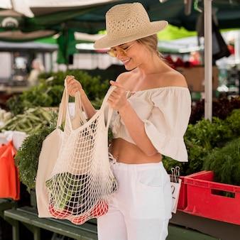 Frau, die in ihre organische tasche schaut