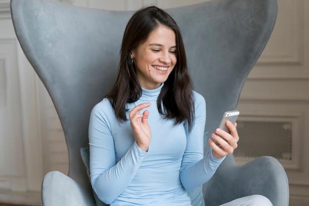 Frau, die in ihrem bett bleibt, während sie einen videoanruf auf ihrem smartphone hat