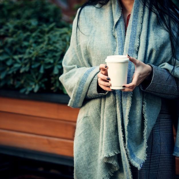 Frau, die in ihren händen einen tasse kaffee 1 hält