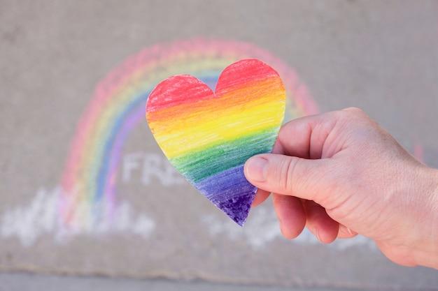 Frau, die in ihren handflächen ein papierherz hält, das in regenbogenfarben des regenbogens der lgbt-gemeinschaft gemalt ist, kreide auf dem bürgersteig, monatsstolz-konzept - temporäre kunst