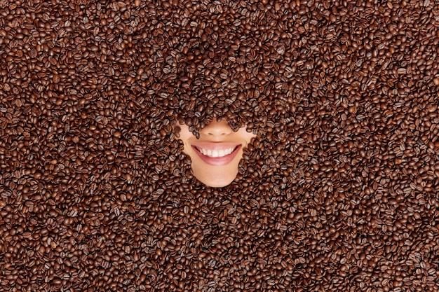 Frau, die in kaffeebohnen ertrunken ist, lächelt breit und zeigt zähne, um ihr lieblingsgetränk zuzubereiten
