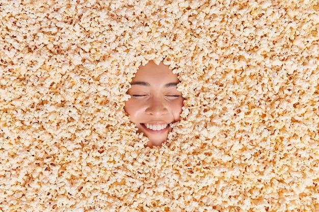 Frau, die in leckerem popcorn begraben ist, lächelt glücklich und zeigt weiße zähne, fühlt sich fröhlich, während sie comedy-filme sieht