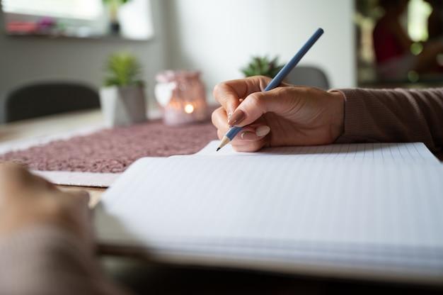 Frau, die in leerem notizbuch auf hölzernem schreibtisch schreibt