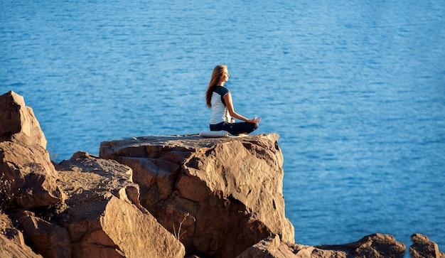 Frau, die in lotus position auf felsen über dem meer sitzt und meditiert. yoga im freien