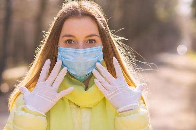 Frau, die in maske und handschuhen in der natur geht. coronavirus schutz. keine leute da. mädchen hält abstand.