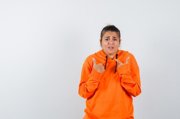 Frau, die in orangefarbenem hoodie auf sich selbst zeigt und verwirrt aussieht
