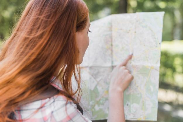 Frau, die in stadtplan zeigt