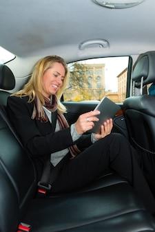 Frau, die in taxi unter verwendung des tablet-computers fährt