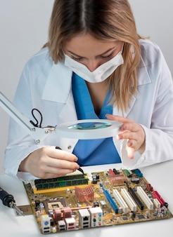 Frau, die in technologie mit maske arbeitet