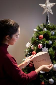 Frau, die in weihnachtsbaumbuchstaben für weihnachtsmann sich setzt