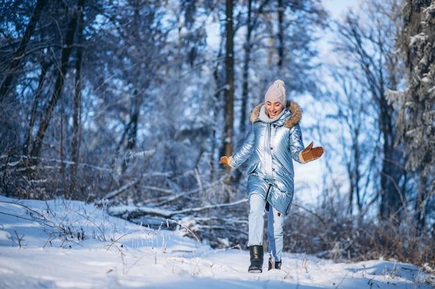 Frau, die in winterpark geht