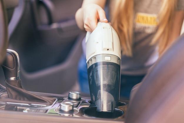 Frau, die innenraum des autos unter verwendung des staubsaugers säubert