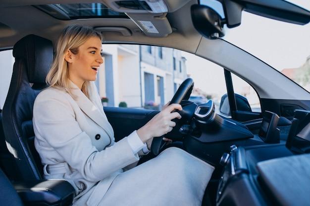 Frau, die innerhalb des elektroautos bei der aufladung sitzt