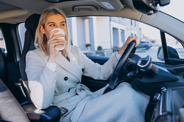 Frau, die innerhalb des elektroautos beim aufladen mit einer kaffeetasse sitzt