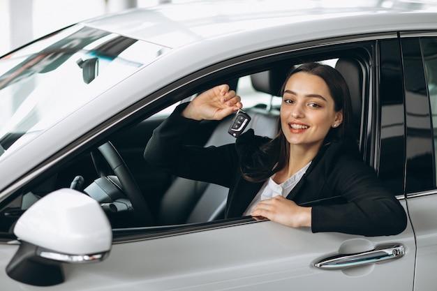 Frau, die innerhalb eines autos sitzt und schlüssel hält