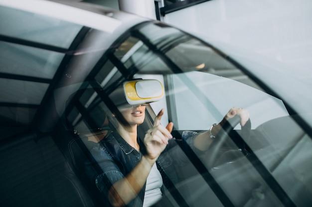 Frau, die innerhalb eines autos trägt vr gläser sitzt