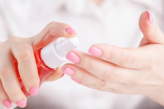 Frau, die insektenschutzmittel auf ihre hand sprüht