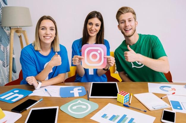 Frau, die instagram hält und ikone mit seinen freunden zeigt thumbup zeichen