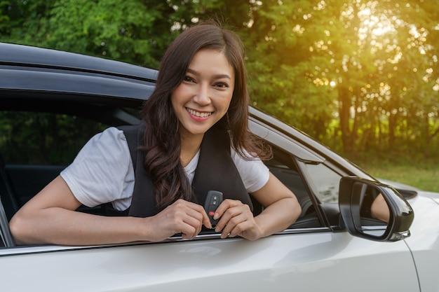 Frau, die intelligente schlüsselfernbedienung mit einem auto hält