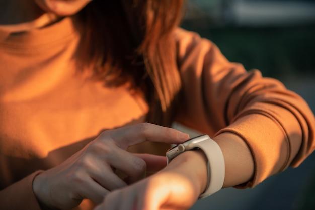 Frau, die intelligente uhren mit prüfendem puls über gesundheitsanwendung verwendet