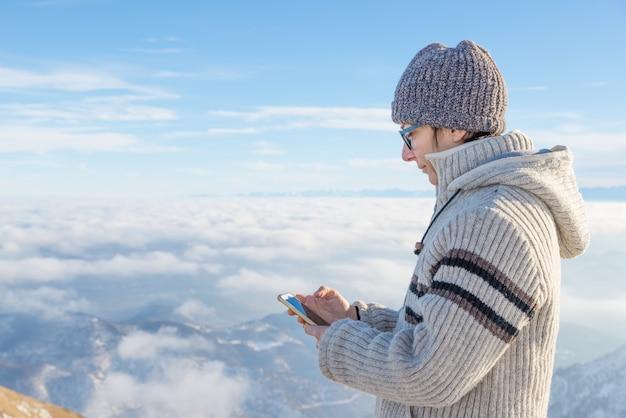 Frau, die intelligentes telefon auf den bergen verwendet.
