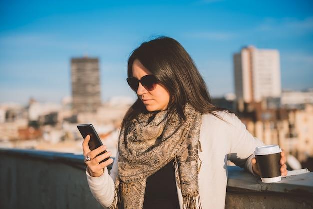 Frau, die intelligentes telefon auf der dachspitze verwendet