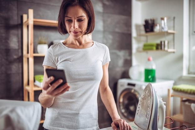 Frau, die intelligentes telefon beim bügeln von kleidung verwendet