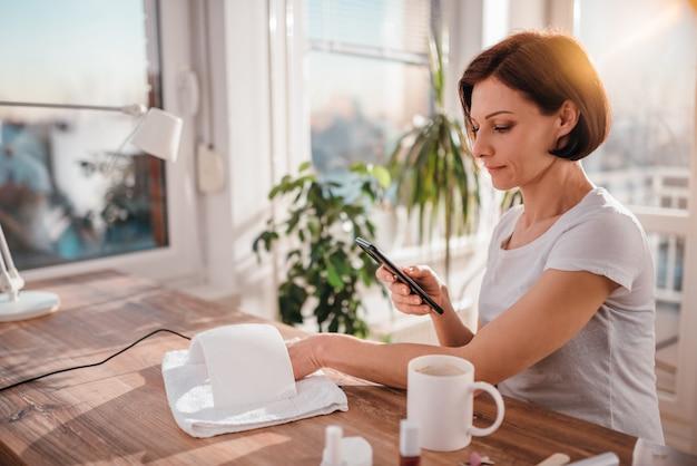 Frau, die intelligentes telefon beim trocknen von nägeln verwendet
