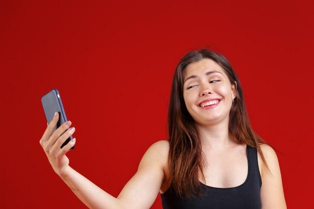 Frau, die intelligentes telefon für das simsen oder das plaudern, lachend mit freude und glücklich verwendet