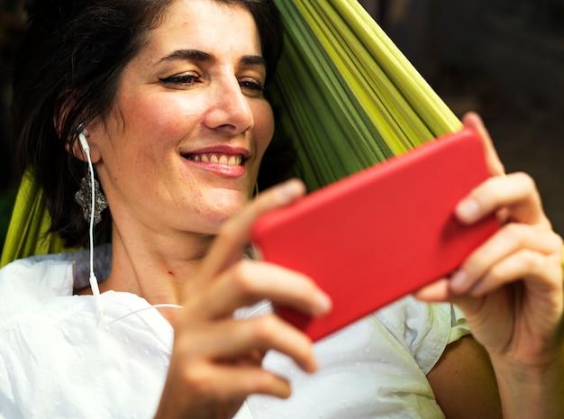Frau, die intelligentes telefon mit dem kopfhörer legt auf hängematte verwendet