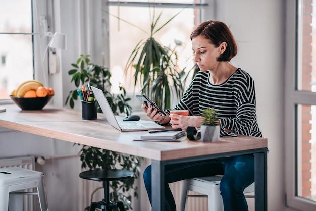 Frau, die intelligentes telefon verwendet und kaffee trinkt