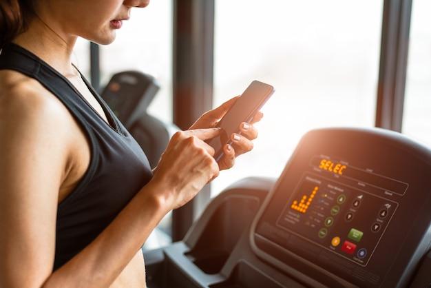 Frau, die intelligentes telefon wenn trainings- oder stärketraining an der eignungsturnhalle verwendet