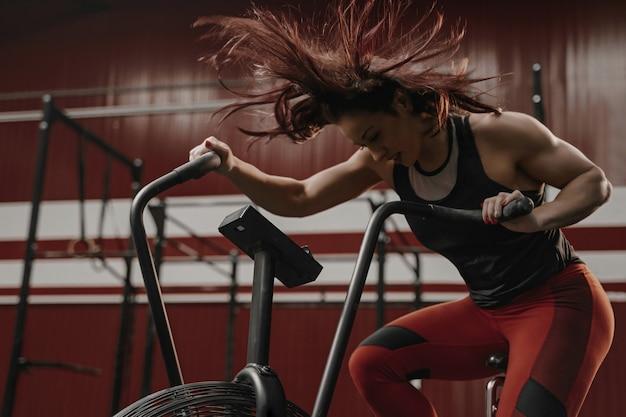 Frau, die intensives cardio-training auf dem übungsrad tut